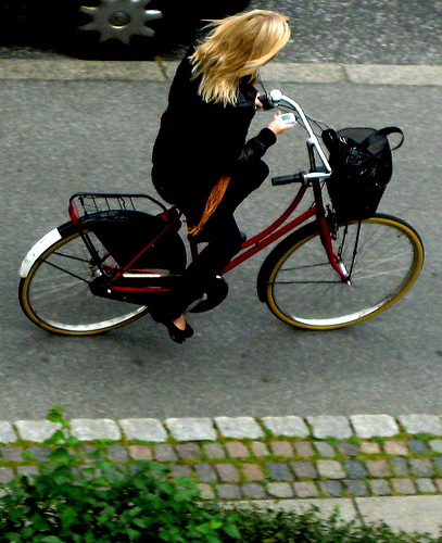 Danish woman cyclist sending text message from mobile phone while cycling